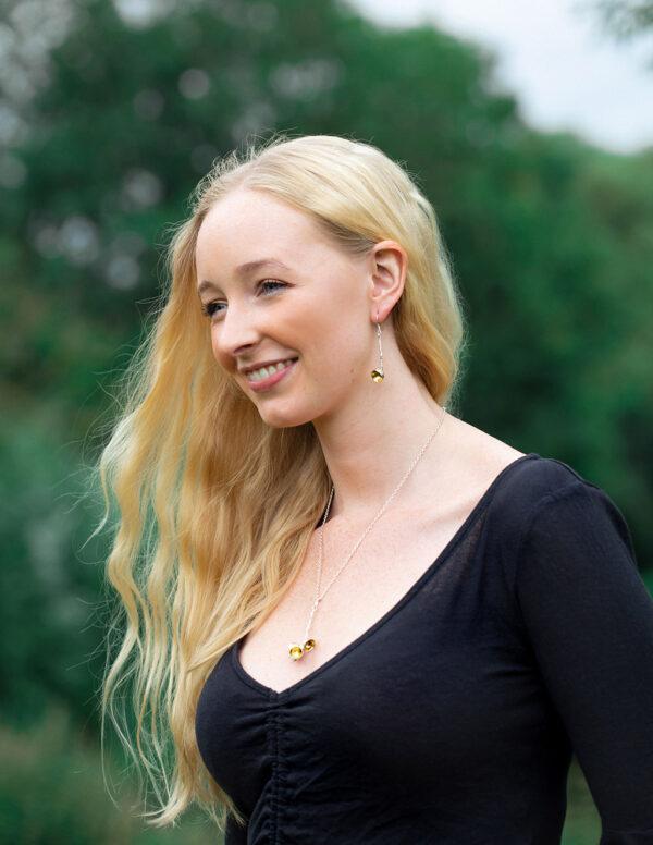 Model wearing horse pendant and snaffle earrings