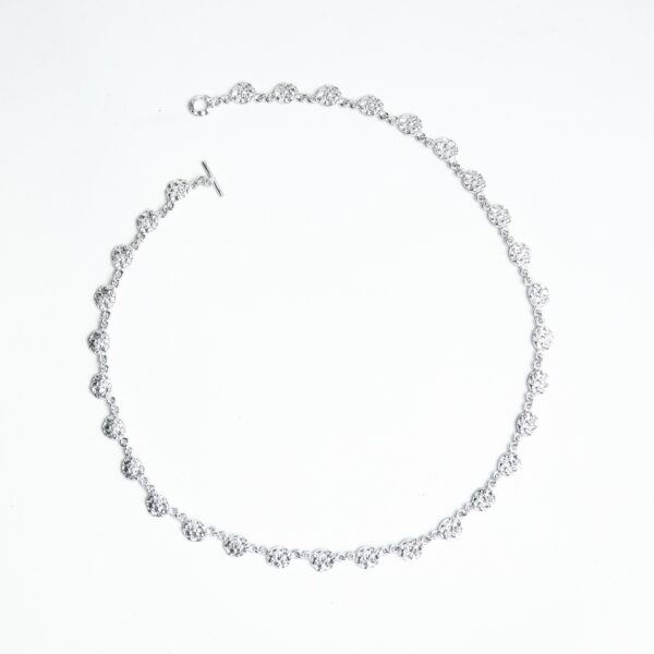Delicate silver necklace texture with the pattern of an acorn cup