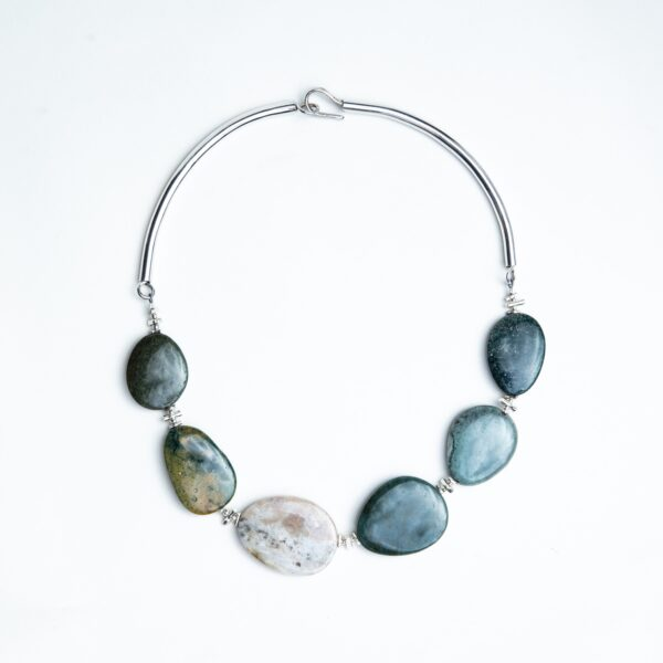 Smooth oval green ocean jasper pebble necklace hanging from a silver hoop