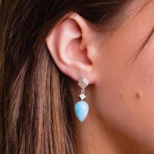 Ear wearing blue larimar earrings
