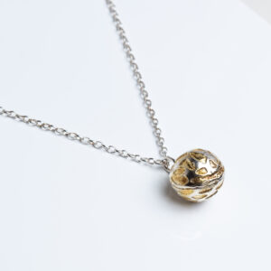 Silver ball pendant with textured surface and gold