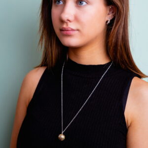 Modal wearing silver ball pendant with gold