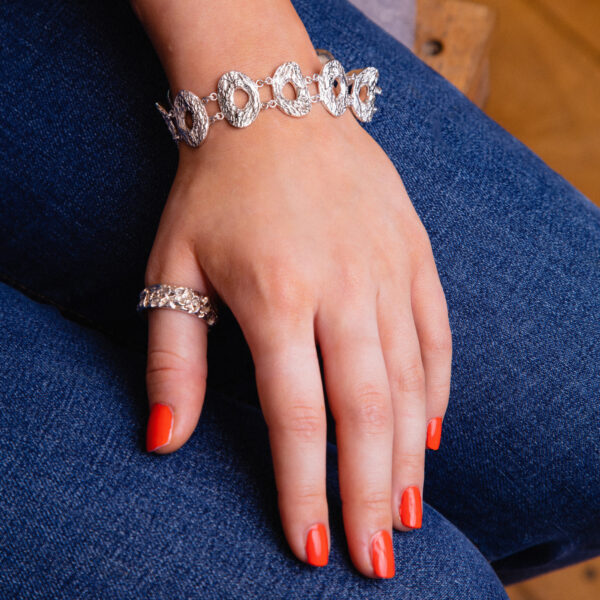 Modal wearing silver chunky cholla wood pattern bracelet and Quince texture ring